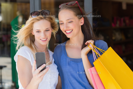 Happy smiling friends looking at smartphoneの素材 [FYI00008988]
