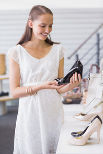 Pretty brunette looking at a heel shoeの写真素材 [FYI00008990]