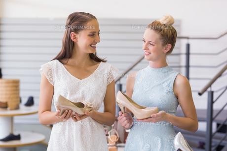 Two happy women holding heel shoesの素材 [FYI00008994]