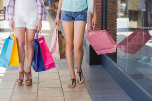 Close up of two women walking with shopping bagsの写真素材 [FYI00008995]