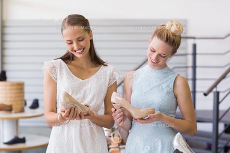 Two happy women holding heel shoesの写真素材 [FYI00008996]