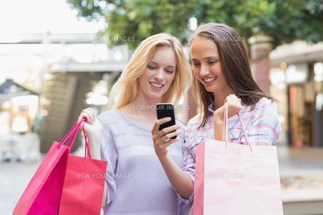 Happy women friends looking at smartphoneの素材 [FYI00008999]