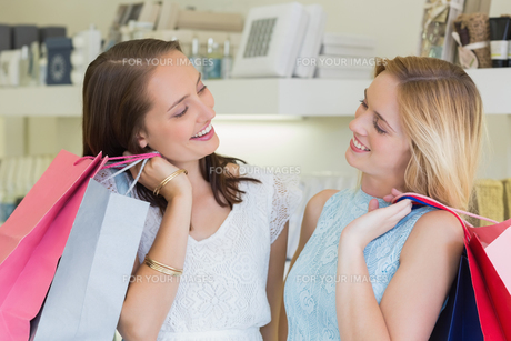 Happy women looking at each other with shopping bagsの写真素材 [FYI00009002]