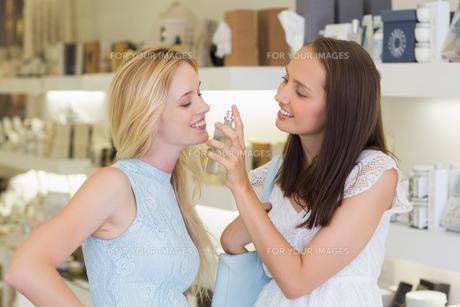 Smiling women spraying perfumeの写真素材 [FYI00009003]