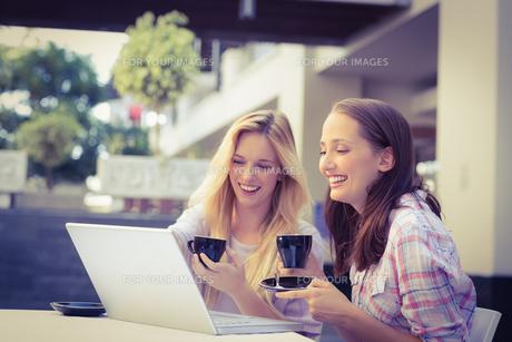 Happy women friends looking at laptopの写真素材 [FYI00009005]
