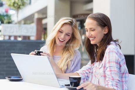 Happy women friends looking at laptopの写真素材 [FYI00009006]