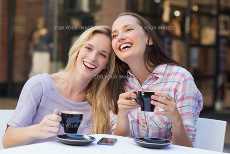 Happy women friends talking and laughing togetherの写真素材 [FYI00009011]