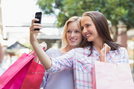 Happy women friends taking a selfie and holding shopping bagsの素材 [FYI00009014]