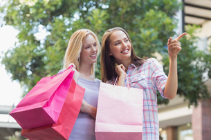 Happy women with shopping bags and pointing awayの写真素材 [FYI00009017]