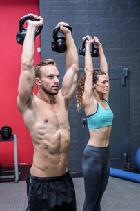 A muscular couple lifting kettlebellsの写真素材 [FYI00009025]
