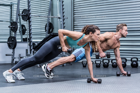 Muscular couple doing plank exercise togetherの写真素材 [FYI00009027]