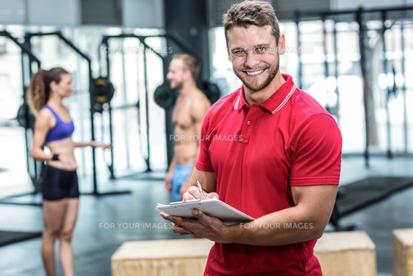 Smiling muscular trainer writing on clipboardの写真素材 [FYI00009031]