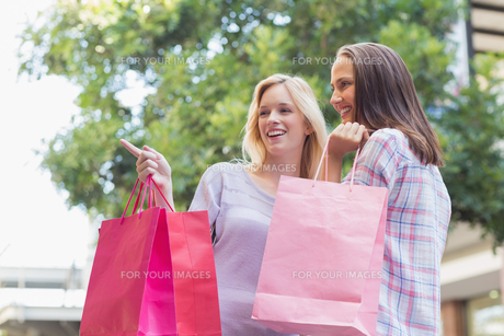 Happy women with shopping bags and pointing awayの写真素材 [FYI00009037]