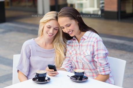 Happy women friends looking at smartphoneの写真素材 [FYI00009038]