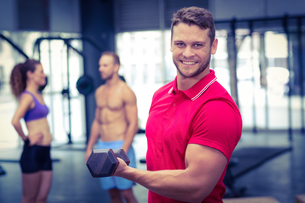 Muscular trainer lifting a dumbbellの写真素材 [FYI00009042]