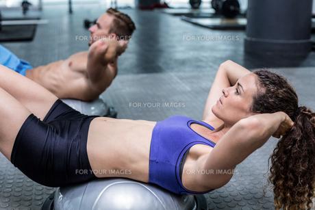 Muscular couple doing bosu ball exercisesの素材 [FYI00009044]