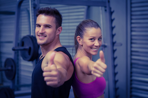 Smiling muscular couple gesturing thumbs upの素材 [FYI00009050]