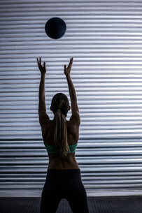 Muscular woman throwing ball in the airの素材 [FYI00009061]