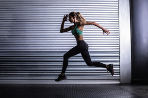 Muscular woman running in exercise roomの写真素材 [FYI00009062]