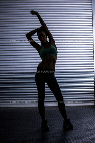 Muscular woman stretching in shadow roomの素材 [FYI00009065]