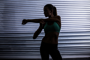 Muscular woman stretching in shadow roomの素材 [FYI00009070]