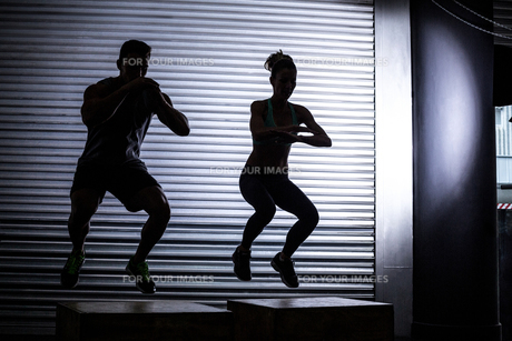 Muscular couple doing jumping squatsの素材 [FYI00009071]