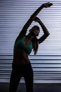 Muscular woman stretching in shadow roomの素材 [FYI00009072]