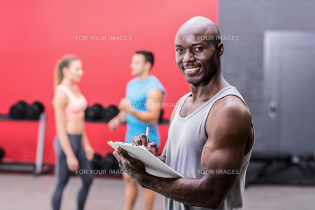 Smiling muscular trainer writing on clipboardの写真素材 [FYI00009079]