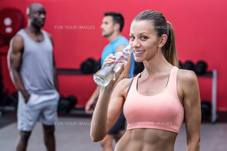Smiling muscular woman drinking waterの写真素材 [FYI00009080]