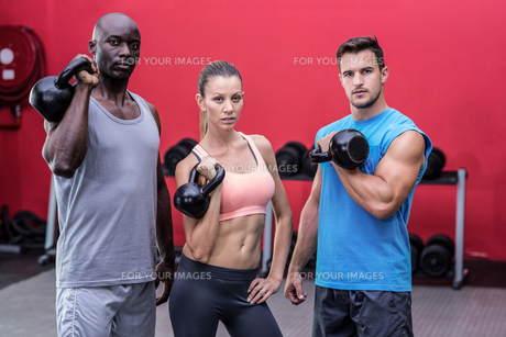 Serious muscular athletes lifting kettlebellsの写真素材 [FYI00009082]