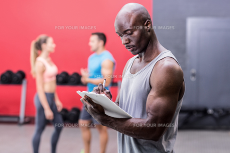 Attentive muscular trainer writing on clipboardの素材 [FYI00009083]