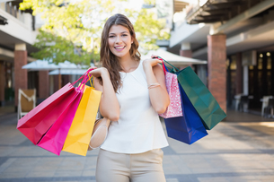 Portrait of smiling woman with shopping bags looking at cameraの素材 [FYI00009089]