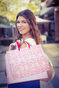 Portrait of smiling woman with shopping bags looking at cameraの素材 [FYI00009091]
