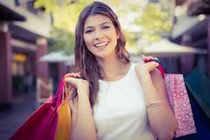 Portrait of smiling woman with shopping bags looking at cameraの素材 [FYI00009096]