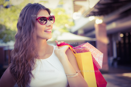 Smiling woman with shopping bags wearing sunglassesの素材 [FYI00009097]