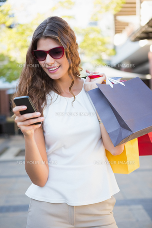 Smiling woman with sunglasses and shopping bags using her smartphoneの素材 [FYI00009098]