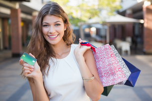 Portrait of smiling woman with shopping bags and credit card looking at cameraの素材 [FYI00009102]