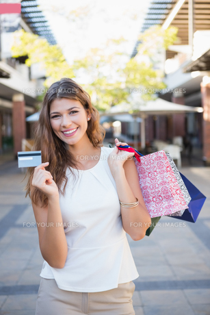 Portrait of smiling woman with shopping bags and credit card looking at cameraの素材 [FYI00009104]