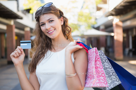 Portrait of smiling woman with shopping bags and credit card looking at cameraの素材 [FYI00009108]