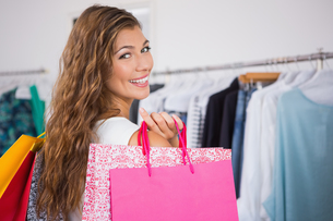 Portrait of smiling woman holding shopping bags and looking at cameraの写真素材 [FYI00009110]