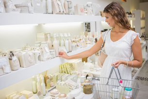 Focused woman with shopping basket browsing productsの写真素材 [FYI00009115]