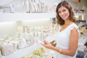 Portrait of smiling woman testing moisturizer and looking at cameraの写真素材 [FYI00009116]