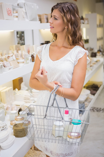 Smiling woman with shopping basket browsing productsの写真素材 [FYI00009120]