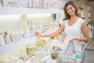 Portrait of smiling woman with shopping basket looking at cameraの写真素材 [FYI00009121]