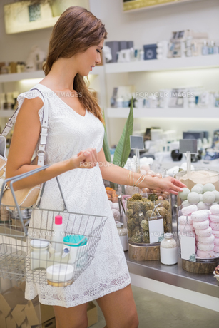 Woman with shopping basket testing soapの写真素材 [FYI00009122]
