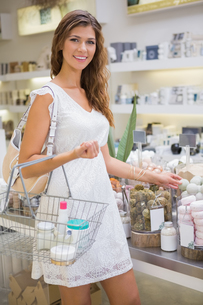 Portrait of smiling woman with shopping basket looking at cameraの写真素材 [FYI00009123]