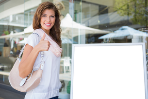 Portrait of smiling woman standing next to blank boardの写真素材 [FYI00009132]