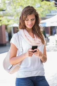 Smiling woman using smartphoneの写真素材 [FYI00009134]