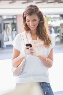 Smiling woman using smartphoneの写真素材 [FYI00009135]