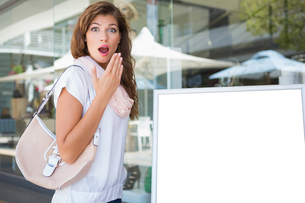 Portrait of surprised woman standing next to a blank boardの写真素材 [FYI00009136]
